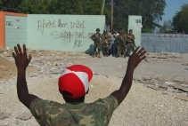 Een vader rijdt met zijn kinderen voorbij een brandende barricade in de Haïtiaanse stad Gonaives. VN-blauwhelmen kunnen in de huidige heksenketel weinig structureels komen doen, denkt Anne Coutteel van de ngo Protos. ,,Een en ander moet eerst uitgevochten