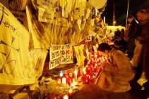 Een vrouw gedenkt bij een rij kaarsen de slachtoffers van de bomaanslagen in Madrid op 11 maart.    <br><br><!--para1-->