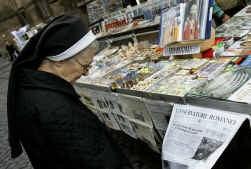 Een non bekijkt in Rome de krantenkoppen na de ziekenhuisopname van de paus donderdag.