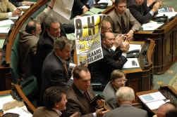 Terwijl Guy Verhofstadt (rechts) een staande ovatie krijgt van de paarse kamerleden, haalt Gerolf Annemans (Vlaams Belang) een B-H-V-affiche boven.