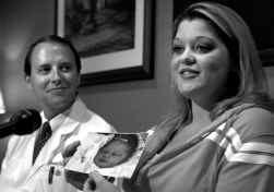 Stephanie Yarber met een foto van haar dochter Anna Grace. Op de achtergrond haar arts, Braden Richmond.
