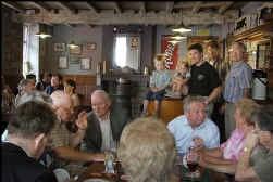 De familie Panneels midden in haar tjokvolle café. Op de toog zitten de kinderen Jan en Ina, achter hen staan broers Yves en Kurt en vader Maurice.