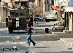 Een Palestijnse jongen vlucht weg voor een van de Israëlische tanks gisteren in Tulkarem.