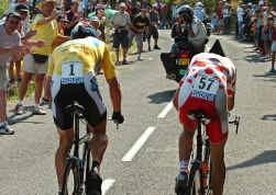 Lance Armstrong steekt pechvogel Mickael Rasmussen voorbij, op weg naar de zege in de tijdrit.