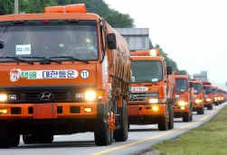 Zuid-Koreaanse vrachtwagens brengen rijst naar het verpauperde Noord-Korea.