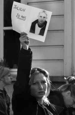 Estelle Dutriez, zus van het slachtoffer, houdt tijdens de protestoptocht van politiemensen een foto van haar doodgeschoten broer omhoog.