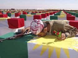 Een Koerdische strijder kust de kist van een van zijn volksgenoten die gevonden werden in een van de vele massagraven en deze herbegraven werden in Arbil.