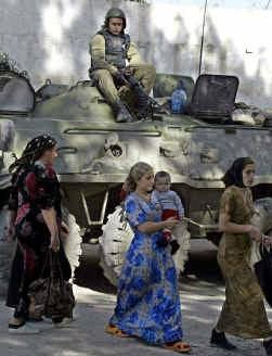 Tsjetsjeense vrouwen stappen voorbij een Russische soldaat in Kurchaloi. Het conflict in Tsjetsjenië begon niet als een religieus geïnspireerde strijd.