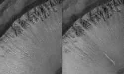 In 2005 (rechts) was er in een geul tegen een kraterwand op Mars een bleke afzetting te zien die er in 1999 (links) nog niet was. Ze lijkt er te zijn gekomen door water.