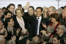 Een opgetogen presidentskandidaat Sarkozy (midden) wuift naar zijn aanhang. Links van hem minister van Defensie Michèle Alliot-Marie.