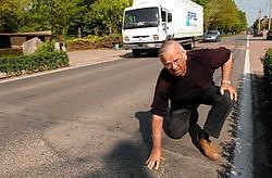 Buurtbewoner Jozef Martelé toont de verzakkingen in de Aartrijkestraat die lawaaioverlast en trillingen veroorzaken. Michel Vanneuville