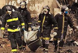 Brandweermannen dragen de stoffelijke resten van een slachtoffer weg. 186 passagiers en bemanningsleden bevonden zich aan boord van het vliegtuig. Ze kwamen allen om het leven.ap<br>