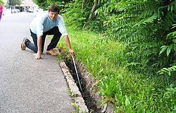 Buurman Herman Christiaan toont de kloof tussen het asfalt en de oever van de Trekweg.kl