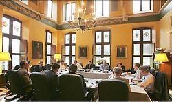 In de grote vergaderzaal zitten de onderhandelaars aan tafels die in een vierkant staan. De vier partijen hebben elk drie onderhandelaars. Photo News<br>