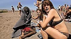 Toeristen bij een uitgeputte Afrikaanse illegale migrant op een strand op het Spaanse eiland Tenerife. ap<br>