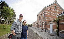 Jo Uytterhoeven en Hilde Pottel voor hun station in rode, gele en zwarte steen. Het is het eindpunt van het fietspad.<br>Jef Collaer<br>