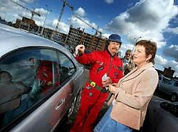 Swa 'de garagist' legt parkeerders uit dat ze hun auto gratis kunnen laten graveren. Yorick Jansens<br>