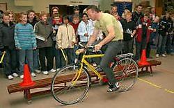 Johan Museeuw kroop op de fiets om de leerlingen te tonen waar gevaren schuilen. Peter Maenhoudt