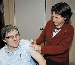 Huisarts Griet Vandemoortele spuit burgemeester Patrick Lansens in met het griepvaccin. Isabelle Vanhassel<br>