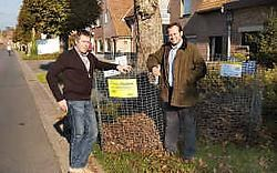 Marnik Verhaeghe (deskundige werkplaatsen) en Giovanni Vandewaetere (groenambtenaar) staan bij de korven onder de door motten aangetaste bomen. Stefaan Beel<br>
