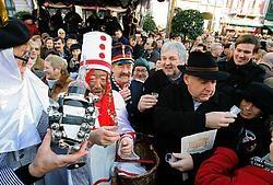 Pierke Pierlala schenkt onder meer burgemeester Termont (dit jaar met opvallende hoed) en schepen van feesten Decaluwe een dreupel in.<br>