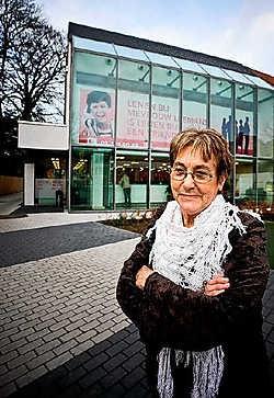 Mevrouw Leemans voor haar nieuwe kantoor aan de Herentalsebaan: 'Die slogan achter mij heb ik zelf bedacht.'Wim Daneels<br>