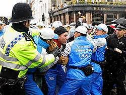 De Chinese veiligheidsagenten houden een betoger in Londen tegen. De oud-atleet Sebastian Coe, die langs het parcours stond, noemt ze 'schurken'. 'Drie keer hebben ze geprobeerd om me weg te duwen. Ze zijn verschrikkelijk.'ap<br>