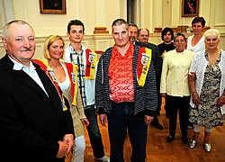 Op de voorgrond voorzitter Henri Van Hoecke van Schuttersmaatschappij Willem Tell, secretaris Cindy Van Hoecke, het jonge lid Nico Schmit en penningmeester Marc Van Hoecke. Op de achtergrond staan enkele leden tijdens de ontvangst in het stadhuis. Koen Me