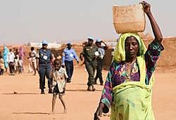 Een vrouw wandelt langs een controlepost van de Verenigde Naties, bij het vluchtelingenkamp Abu Shouk (Noord-Darfour). De VN-vredesmissie is verlengd, maar haar opdracht blijft ambigu en dus bedreigd.ap<br>