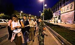 Een veiligheidsagent in Kashgar houdt journalisten en bewoners weg van de plaats van de bloedige aanslag waarbij zestien politiemannen gedood werden.reuters<br>