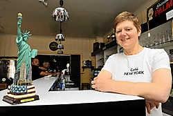 Rita Van Ryckeghem houdt Café New York open: 'Vooral vanaf de jaren 1880 zijn veel Doomkerkenaren uitgeweken, twee op de drie inwoners vertrokken toen met de Red Starline en hun ticket kochten ze hier.'<br>