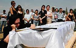 Yulia Klimchuk bij de kist van haar zoon, fotojournalist Alexander Klimchuk, die stierf tijdens het conflict.reuters<br>