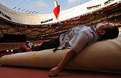 Een Chinese arbeider rust even uit in het Vogelnest, het Nationaal Stadion in Peking, waar gisteren opgeruimd werd na de slotceremonie van de Olympische Spelen, zondag. Een laatste groep Belgische atleten, onder wie de vijf medaillewinnaars, werd vanmorge