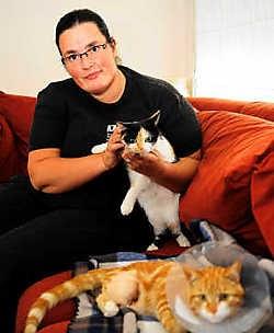 Sylvie Denancy met haar jongste kat. De dierenarts moest de poot van het mishandelde beestje amputeren. Florian Van Eenoo