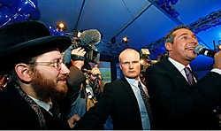 Een orthodoxe joodse man die na de verkiezingen in de buurt van Heinz-Christian Strache (rechts) tracht te komen, wordt tegengehouden door een van diens bodyguards.afp<br>