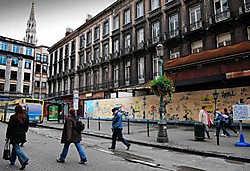 De gebouwen vlakbij het Beursgebouw staan er al jaren zwaar verkommerd bij, zij het keurig verstopt achter een kleurrijke stripwand.Herman Ricour<br>
