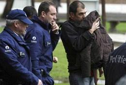 Politiemensen begeleiden Bart naar zijn wagen. Zijn dochterje zit onder de jas van zijn vriendin.