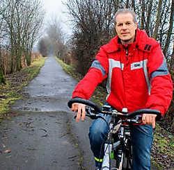 Voorzitter van de Fietsersbond Patrick Vandemenschbrugge toont een beschadigde strook op het Mijnwerkerspad: 'De boomwortels maken fietsen gevaarlijk.' edp