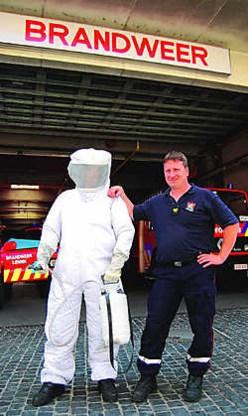 Wouter Moonens, brandweerman van het korps van Lennik met naast hem een collega in een beschermend pak dat de mannen aandoen als ze de wespennesten verdelgen. Jelle Schepers