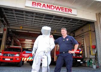 Wouter Moonens, brandweerman van het korps van Lennik met naast hem een collega in een beschermend pak voor de brandweerlieden. Jelle Schepers