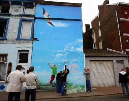 Een reuzenfoto van een spelend kind verbergt het gruwelhuis. belga