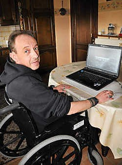 Marc Van Aerschot voor zijn pc die de metalen implantaten in zijn schouder weergeeft.Fernand Goyens