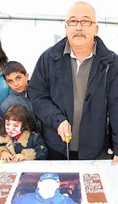 Leon Bernac snijdt de taart aan die hij kreeg van de buurtvaders.<br> Paul Van Moll