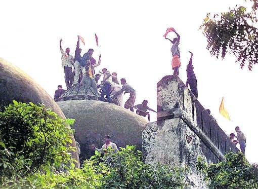 Fanatieke hindoes op het dak van de Babri Masjid moskee, enkele uren voor ze vernield zou worden.afp