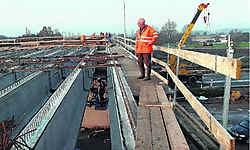 Schepen van Openbare Werken Pierre De Bock boven op de nieuwe brug die over de E34 werd gelegd en volop in de fase van afwerking zit. gdr
