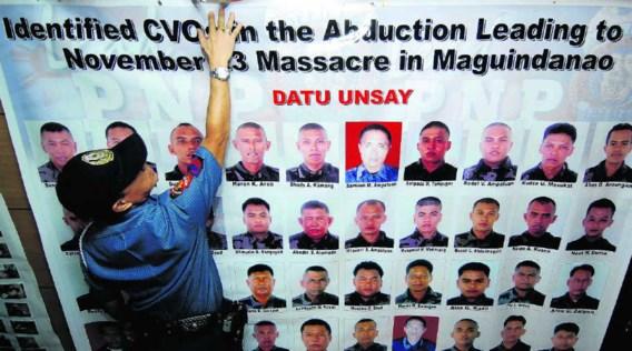 Een politieman hangt een affiche op met de foto's van honderd gezochte leden van de Ampatuan-militie, die beschuldigd wordt van politieke moorden. afp