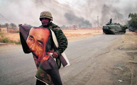 Een Amerikaanse soldaat verscheurt een poster van Saddam in Irak in 2003. De VS en Groot-Brittannië verdachten Irak van het bezit van massavernietigingswapens en vielen het land officieel daarom aan. photo news