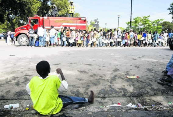 Haïtianen schuiven in de hoofdstad Port-au-Prince massaal aan bij een brandweerwagen waar water bedeeld wordt. afp