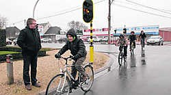 Jan Jonckheere kijkt toe hoe jonge fietsers veilig het kruispunt kunnen oversteken. mvn