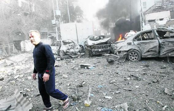 Een man wandelt tussen de brokstukken in de buurt van het Hamra-hotelinBagdad. Analisten zien in de aanslagen een poging om de Iraakse premier Nouri al-Maliki te verzwakken.epa
